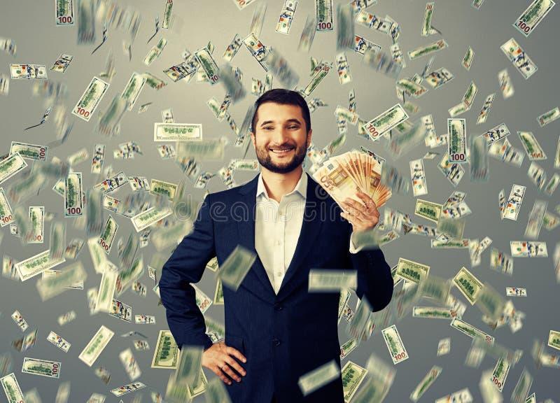 Gelukkige zakenman die zich onder geldregen bevinden stock afbeeldingen