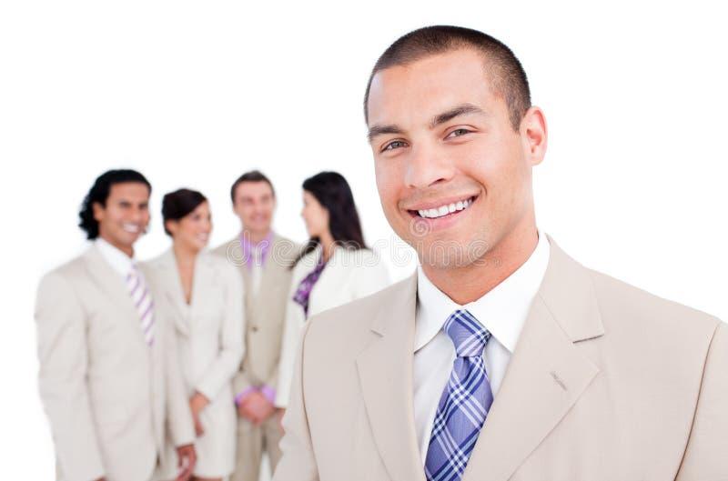 Gelukkige zakenman die zich voor zijn team bevindt royalty-vrije stock afbeelding