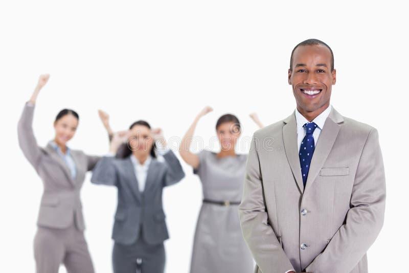 Gelukkige zakenman met enthousiaste medewerkers op de achtergrond stock afbeelding