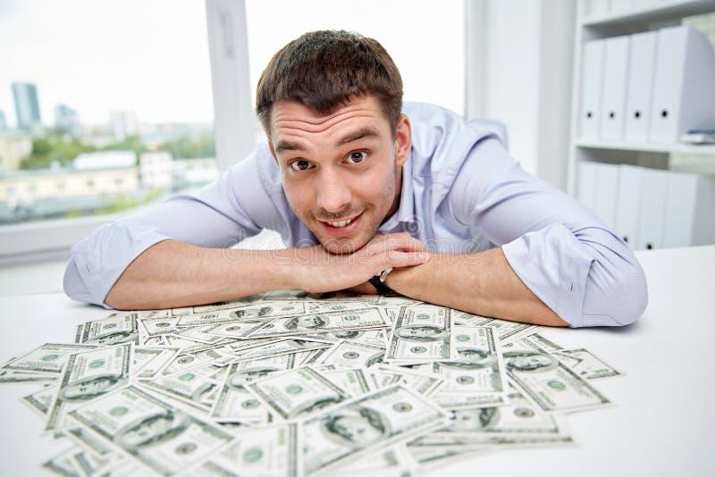 Gelukkige zakenman met hoop van geld in bureau stock fotografie