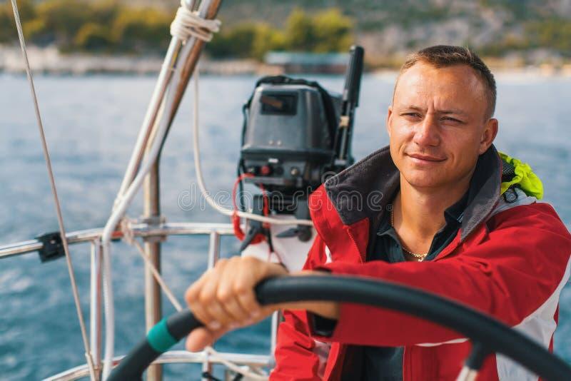 Gelukkige zeeman bij het roer van zijn varend jacht Sport royalty-vrije stock foto's
