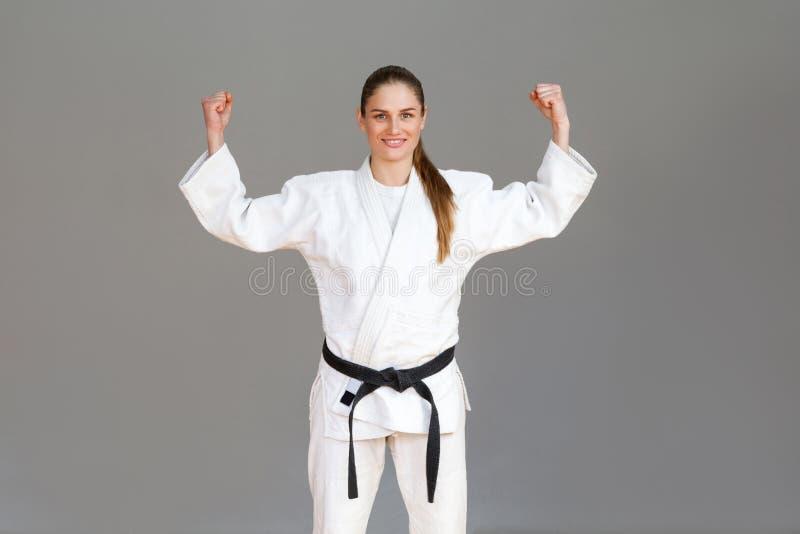 Gelukkige zekere atletische jonge vrouw in witte kimono en zwarte B stock afbeeldingen