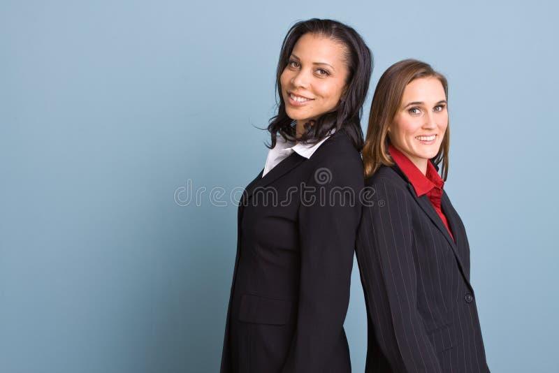 Gelukkige zekere onderneemsters die op het werk glimlachen stock foto
