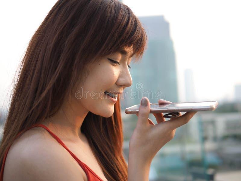 Gelukkige zekere vrouw die op de mobiele celtelefoon spreken op speakerphone stock foto