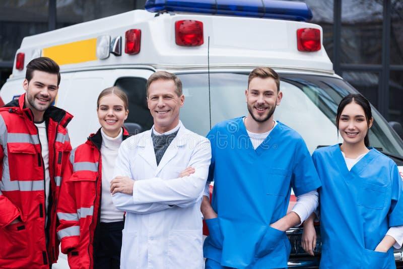 gelukkige ziekenwagen artsen die team werken die zich vooraan bevinden stock foto