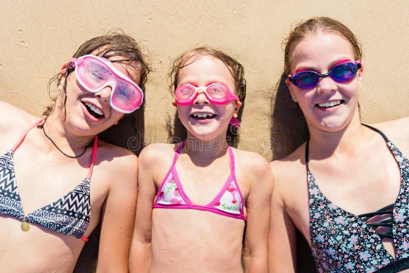 Gelukkige zusters die pret op het strand hebben De zomervakantie en reisconcept royalty-vrije stock fotografie