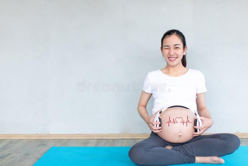 Gelukkige zwangere Aziatische vrouw die hoofdtelefoons toepassen op haar buik voor prenatale muziekstimulatie Muziek en Emotiecon stock afbeeldingen