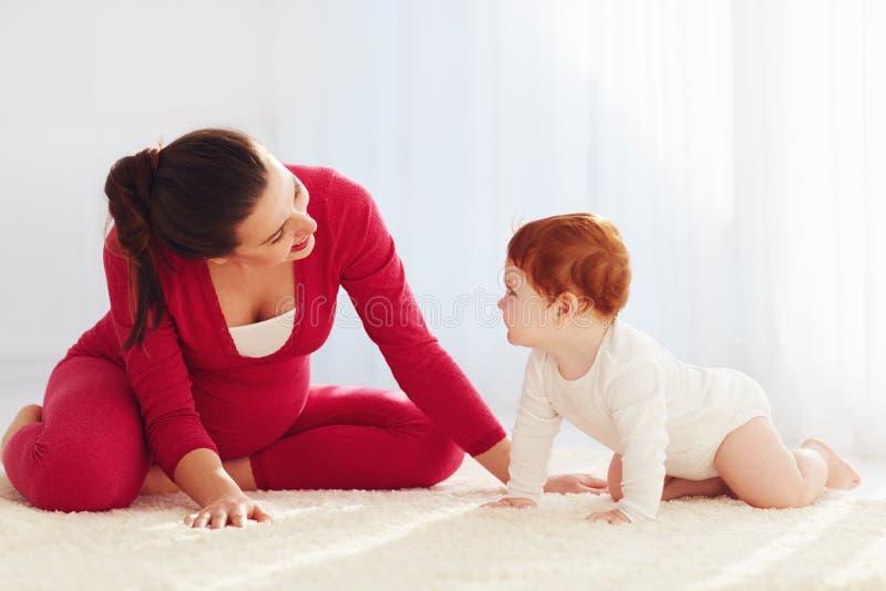 Gelukkige zwangere moeder en peuterbaby die thuis spelen stock afbeeldingen