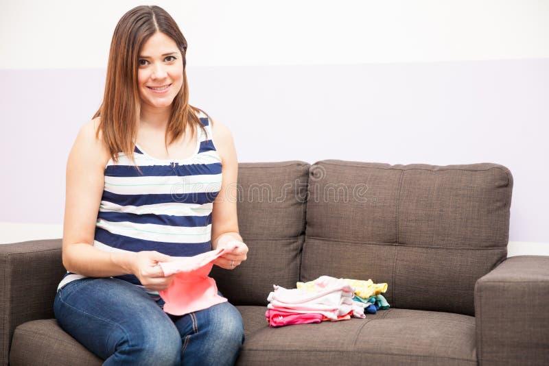 Gelukkige zwangere vrouw die babykleren vouwen stock afbeelding