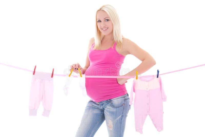 Gelukkige zwangere vrouw die die uit kindkleren hangen op wit worden geïsoleerd stock afbeelding