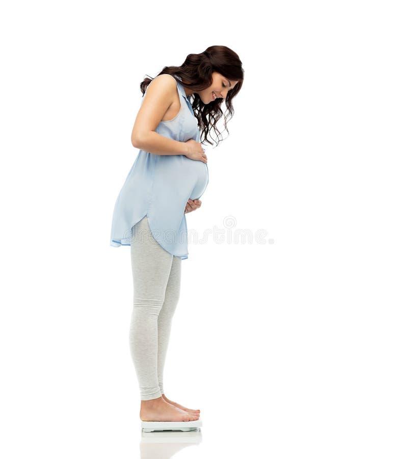 Gelukkige zwangere vrouw die gewicht op schalen meten stock afbeeldingen