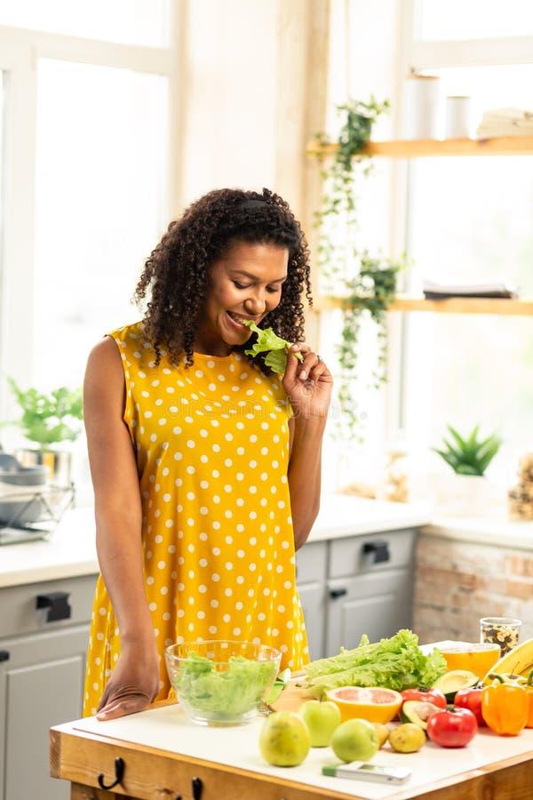 Gelukkige zwangere vrouw die sla in haar keuken eten royalty-vrije stock foto's