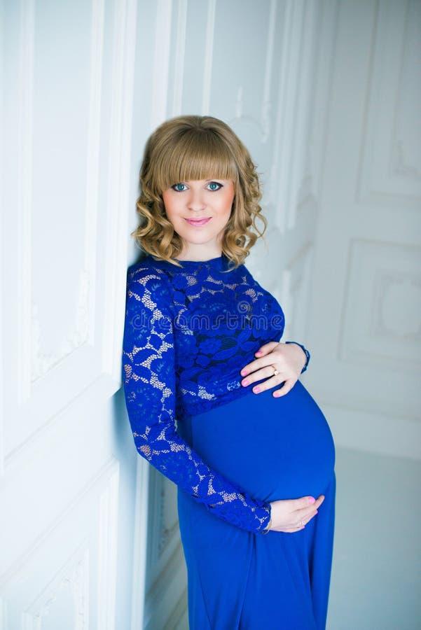 Gelukkige zwangere vrouw in het blauwe kleding stellen in studio stock afbeelding