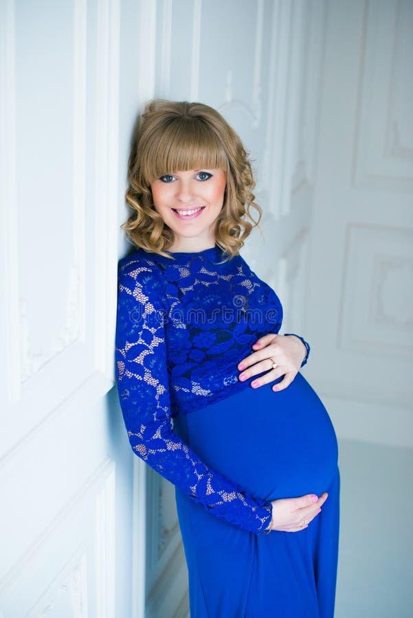Gelukkige zwangere vrouw in het blauwe kleding stellen in studio royalty-vrije stock afbeelding
