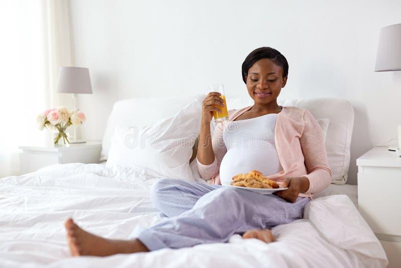 Gelukkige zwangere vrouw met croissantbroodjes thuis stock foto