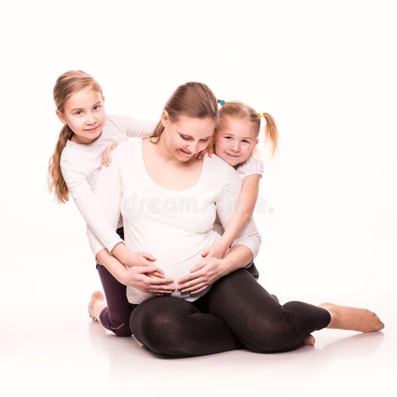 Gelukkige zwangere vrouw met haar jonge geitjes stock afbeeldingen