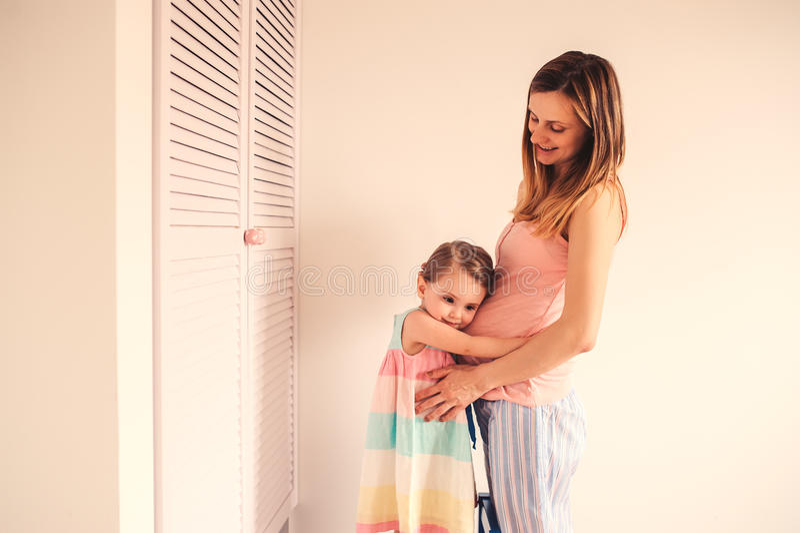 Gelukkige zwangere vrouw met haar peuterdochter thuis stock foto