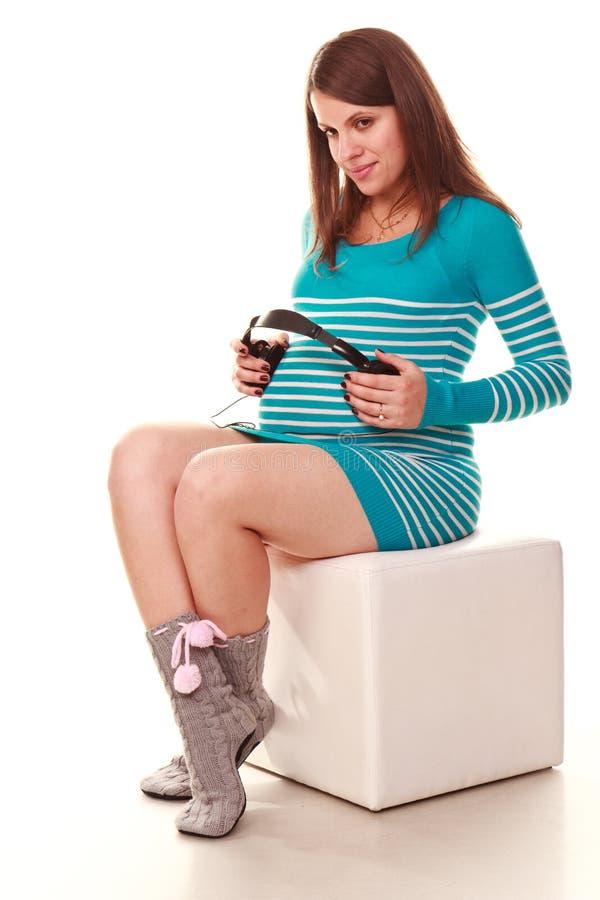 Gelukkige zwangere vrouw met hoofdtelefoons royalty-vrije stock afbeelding