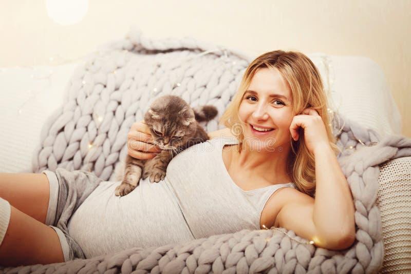 Gelukkige zwangere vrouw met kat op een bank royalty-vrije stock fotografie