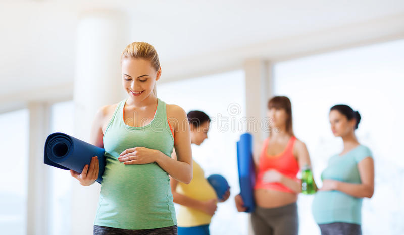 Gelukkige zwangere vrouw met mat in gymnastiek stock afbeeldingen