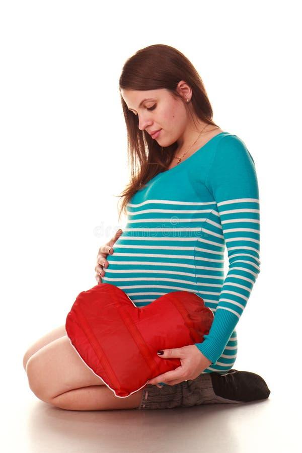 Gelukkige zwangere vrouw met rood hart stock afbeeldingen