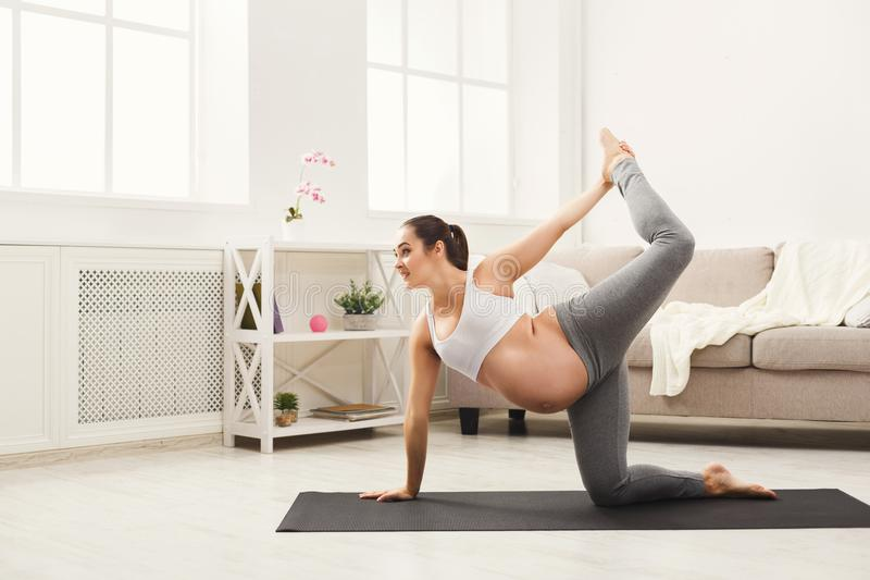 Gelukkige zwangere vrouw opleidingsyoga thuis stock fotografie