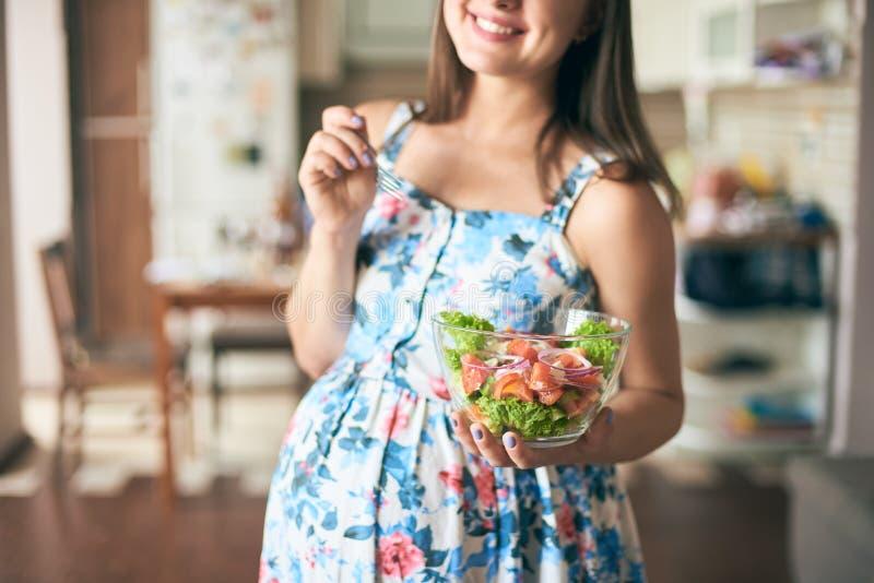 Gelukkige zwangere vrouwelijke houdende plaat met groenten royalty-vrije stock fotografie