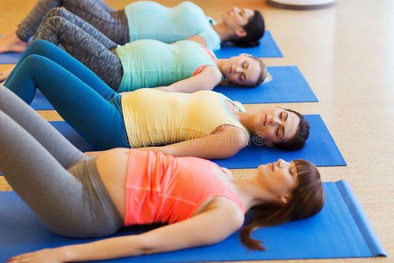 Gelukkige zwangere vrouwen die op matten in gymnastiek uitoefenen royalty-vrije stock afbeeldingen