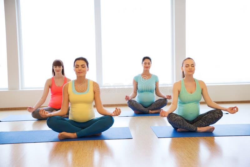 Gelukkige zwangere vrouwen die yoga in gymnastiek uitoefenen stock foto's