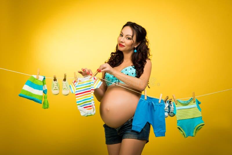 Gelukkige zwangere vrouwen hangende kleren voor de toekomstige baby Het wachten op de baby Speld op Stijl royalty-vrije stock fotografie