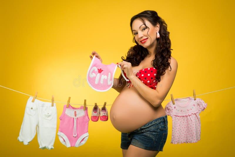Gelukkige zwangere vrouwen hangende kleren voor de toekomstige baby Het wachten op de baby Speld op Stijl royalty-vrije stock afbeeldingen