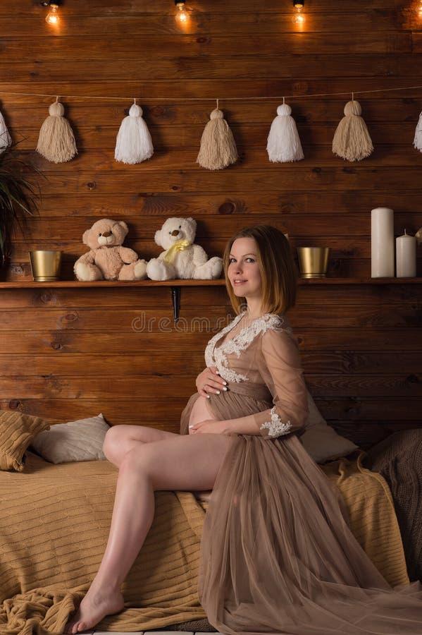 Gelukkige zwangere vrouwenzitting op het bed stock afbeelding