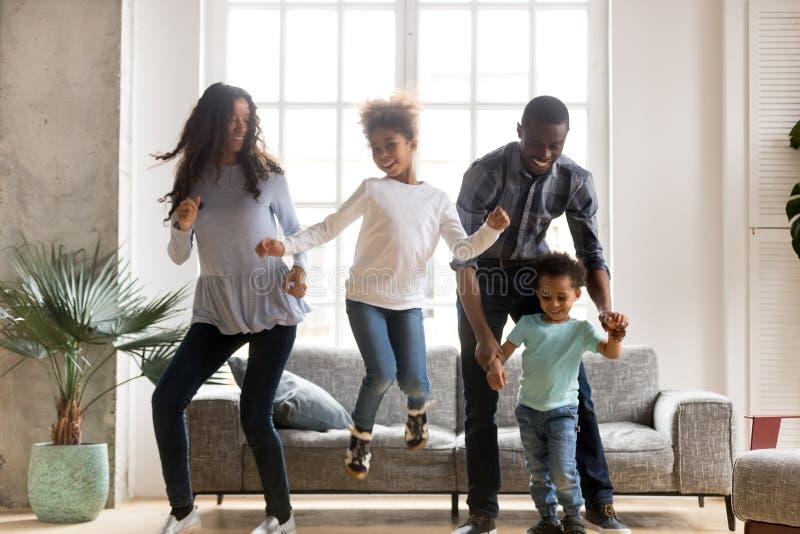 Gelukkige zwarte Afrikaanse familie die thuis dansen royalty-vrije stock foto's