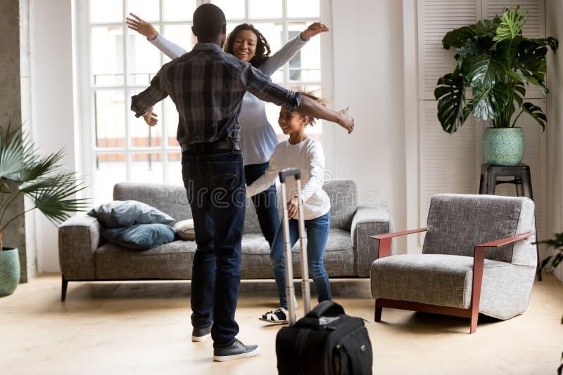 Gelukkige zwarte die familie wordt opgewekt om papa te ontmoeten die naar huis komen stock afbeelding