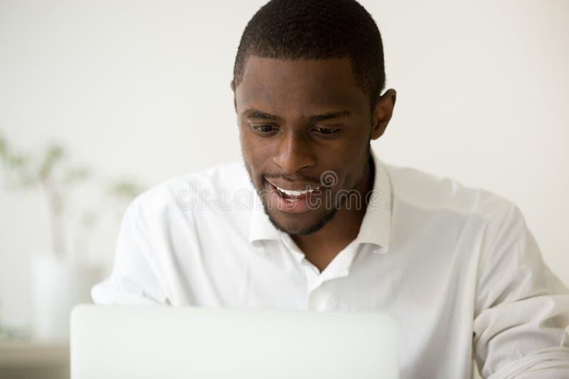 Gelukkige zwarte die manager met goed bedrijfnieuws online wordt opgewekt royalty-vrije stock afbeelding