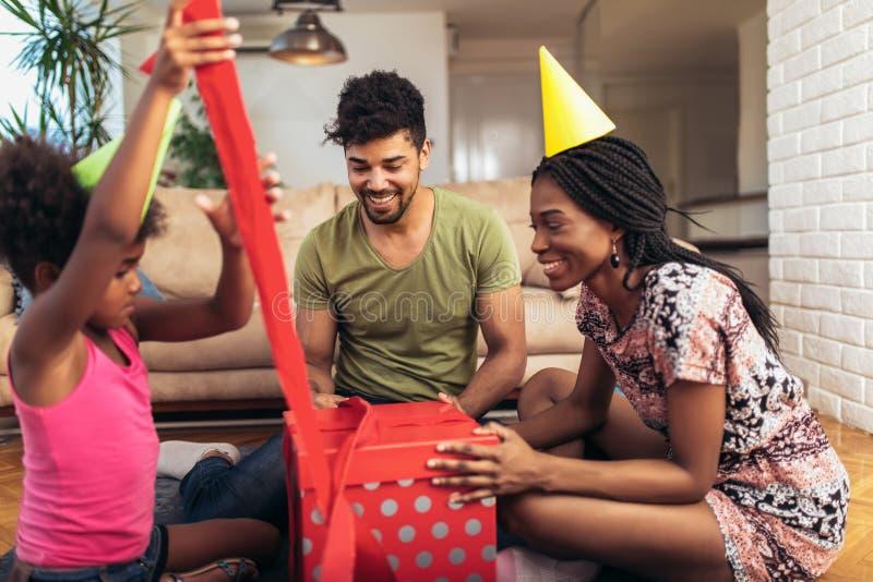 Gelukkige zwarte familie thuis Afrikaanse Amerikaanse vader, moeder en kind het vieren verjaardag, die pret hebben bij partij stock afbeeldingen