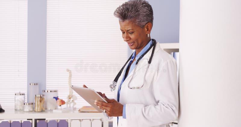 Gelukkige Zwarte Hogere arts die zich in bureau met tablet bevinden stock foto