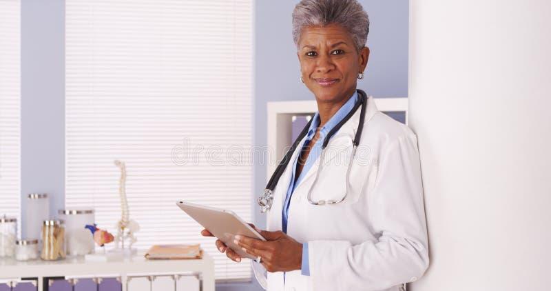 Gelukkige Zwarte Hogere arts die zich in bureau met tablet bevinden stock foto's