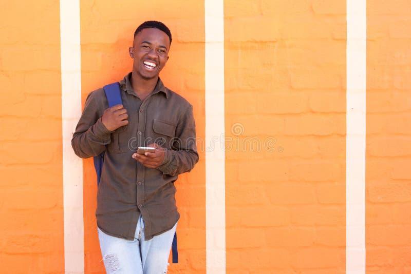Gelukkige zwarte kerel die met celtelefoon tegen oranje muur lacht royalty-vrije stock afbeelding