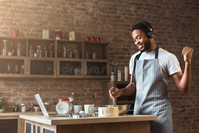 Gelukkige zwarte mens die in oortelefoons aan muziek luisteren terwijl het bakken royalty-vrije stock afbeeldingen