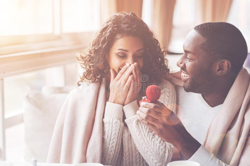 Gelukkige zwarte mens die ring geven aan zijn bruid stock foto