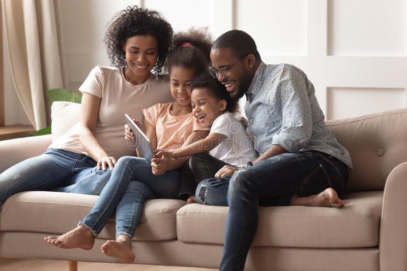 Gelukkige zwarte ouders en kinderen die digitale tablet op bank gebruiken royalty-vrije stock afbeelding