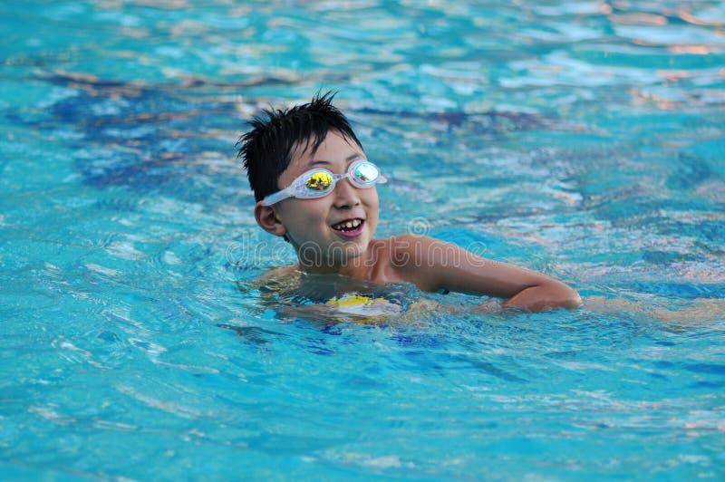 Gelukkige zwemmende jongen stock foto's