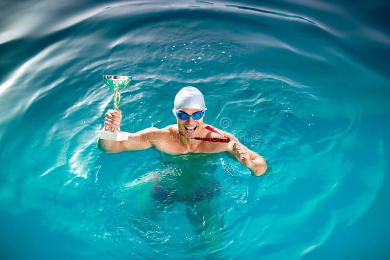 Gelukkige zwemmer met drinkbeker en medaille stock foto