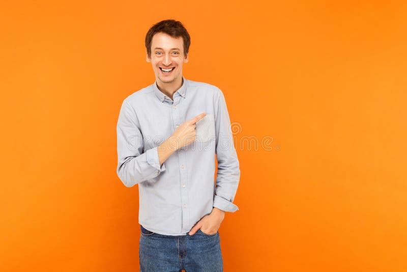 Gelukmens die vinger richten op exemplaar ruimte en toothy glimlach stock foto