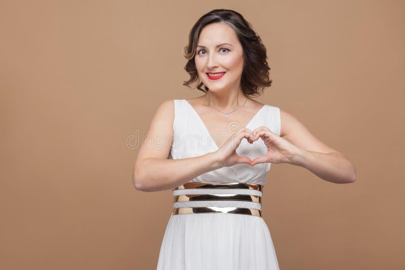 Gelukvrouw die hartvorm tonen door handen royalty-vrije stock afbeelding