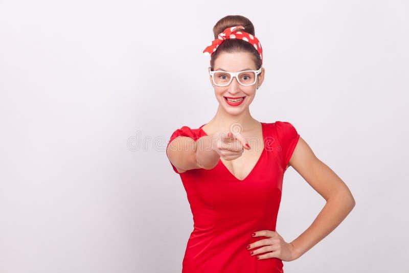 Gelukvrouw die in rode kleding vinger richten een toothy glimlach royalty-vrije stock afbeelding