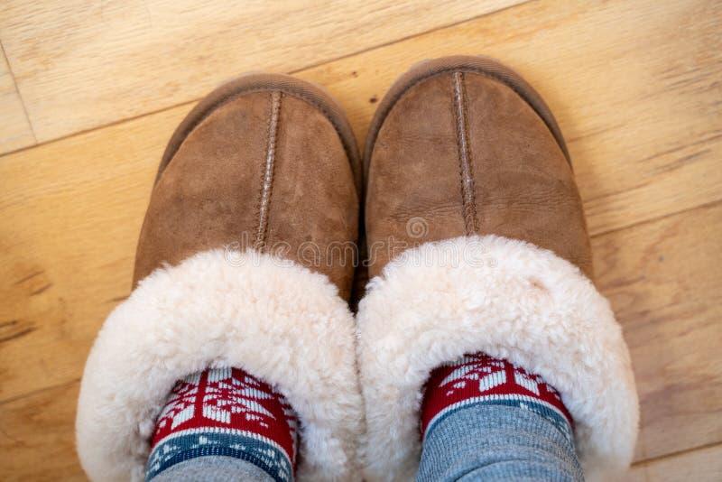 Gemütliches sherpa stricken lederne Haus slipperes mit warmem Socken Füße in den Pantoffeln auf Holzfußboden Raum für Exemplarpla lizenzfreie stockbilder