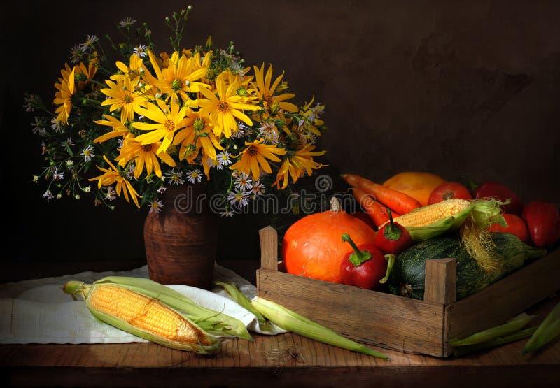 Gemüse in einer Holzkiste und in den Blumen auf einer Tabelle lizenzfreie stockbilder