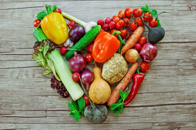 Gemüse in Form des Herzens auf hölzernem Schreibtisch stockfoto